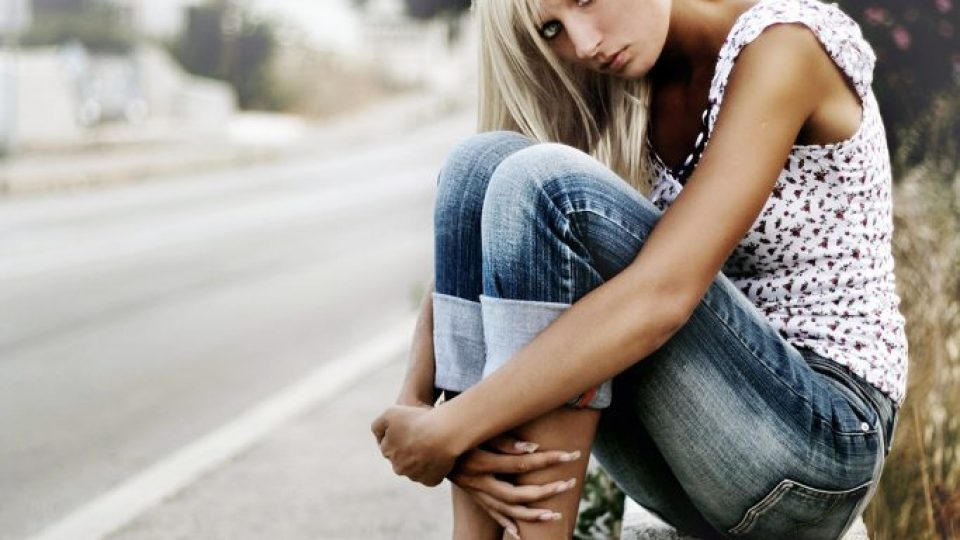 Young blonde sitting by the road